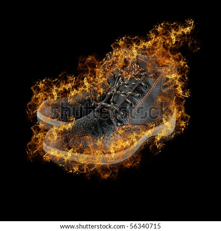 moist modern working boots at fire isolated on a black background - stock photo