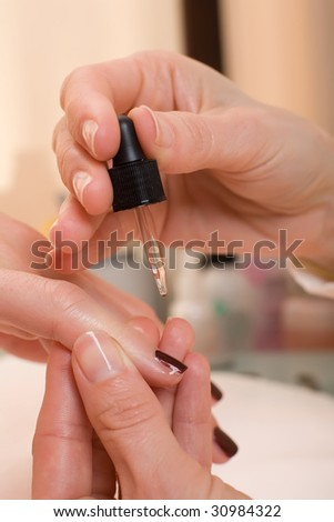 Moisteriser being applied to a womans finger nail.