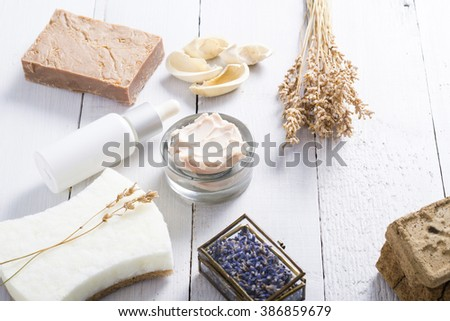 moisturizer, organic soap, henna blocks, dropper, sponge, and dried lavenders on white wood table background