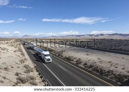 MOJAVE DESERT, CALIFORNIA, USA - October 6, 2015:  Constant truck and tourist traffic in Interstate 15 between Los Angeles and Los Vegas in California's Mojave Desert.   - stock photo
