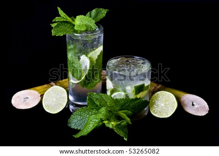 Mojito and Caipirinha over black background, garnished with mint leaves, lemon and Sugar cane. - stock photo