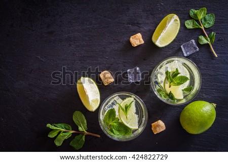 Mojito and ingredients, dark stone background - stock photo
