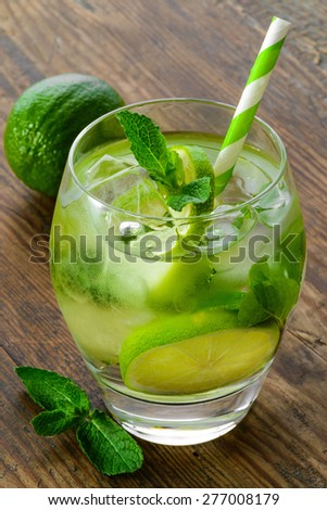 mojito cocktail and fresh ingredients on brown wooden table - stock photo