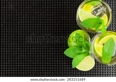 Mojito cocktail and ingredients over black rubber mat with copy space - stock photo