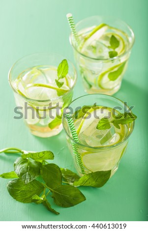 mojito cocktail and ingredients over green background