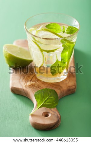mojito cocktail and ingredients over green background - stock photo