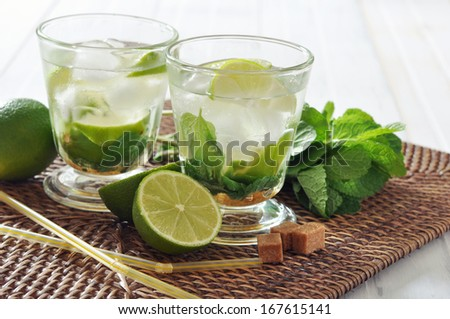 Mojito cocktail in glass with lime and mint on wicker place mat - stock photo