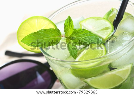 Mojito cocktail made of white rum, ice cubes, sugar, mint leaves and limes with a black drinking straw and sunglasses in the back (Selective Focus, Focus on the front of the mint leaf) - stock photo