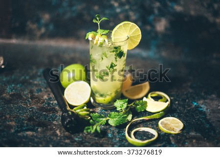 mojito cocktail with lemon and limes garnish. alcoholic drink at bar with vintage effect - stock photo