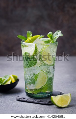 Mojito cocktail with lime and mint in highball glass on a grey stone background - stock photo
