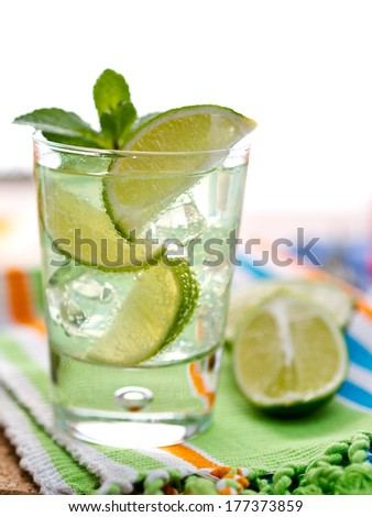 Mojito cocktail with wedges of lime and mint leaves