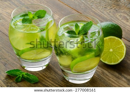 mojito cocktails and fresh ingredients on brown wooden table - stock photo
