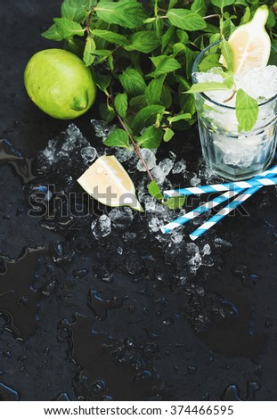 Mojito cooking set. Bunch of fresh mint, lime, chipped ice and cocktail glass over black slate stone backdrop, selective focus, copy space - stock photo
