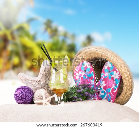 Mojito drink, straw Hat, sunglasses and flip-flops with tropical beach background, summer accessories - stock photo