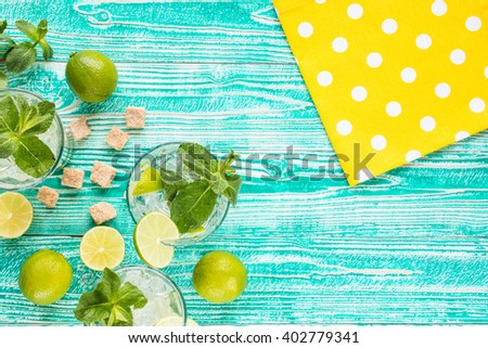 mojito in glasses with ice cubes,  decorated by mint leaf, lime fruits, yellow napkin at white polka dots on turquoise colored wooden table, top view - stock photo