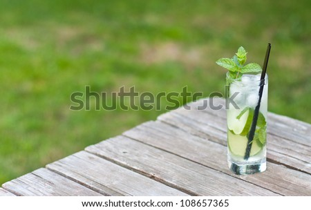 mojito served on a picnic table on a nice sunny day with green grass - stock photo