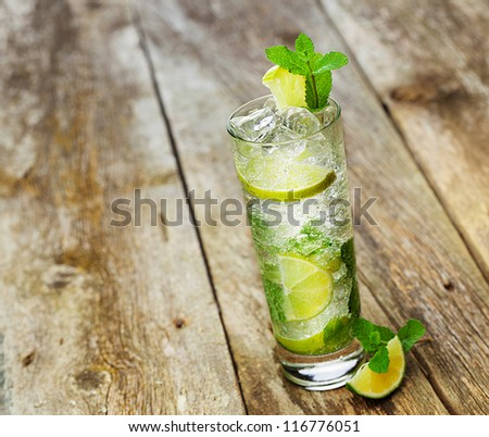 Mojito with a slice of lime on a wooden table - stock photo