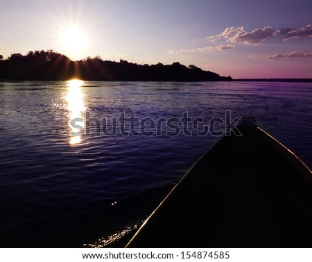 Mokoro canoe trip - traditional tourist attraction in Botswana and northern Namibia (here - during the sunset in Caprivi Strip) - stock photo
