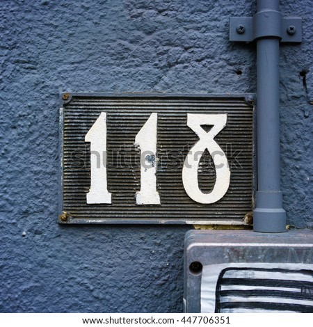 Molded house number one hundred and eighteen - stock photo