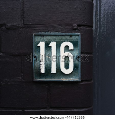 molded house number one hundred and sixteen - stock photo