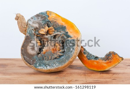 Moldy pumpkins and seeds on the table - stock photo