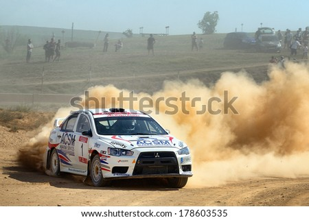 MOLLERUSSA, SAPIN - AUG 31: Spanish driver Xevi Pons and his codriver Xavier Amigo in a Mitsubishi Lancer Evo X race in the 4th Rally Pla d'Urgell, on Aug 31, 2013 in Mollerussa, Spain. - stock photo