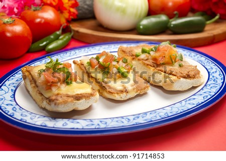 Molletes Mexican Dish. Made with bolillos sliced and spread with beans and topped with cheese. Grilled in an oven until the cheese melts and served with salsa pico de gallo.