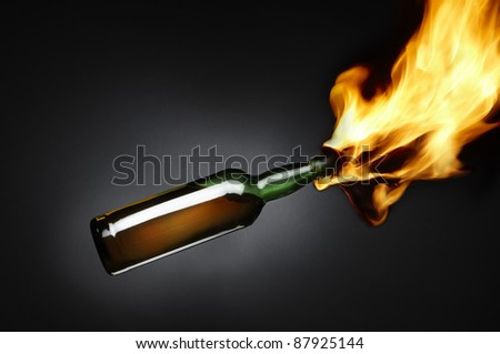 Molotov cocktail depicts flames shooting out of bottle filled with flammable liquid includes space for copy. - stock photo