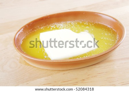 molten creamy butter in bowl over wood - stock photo