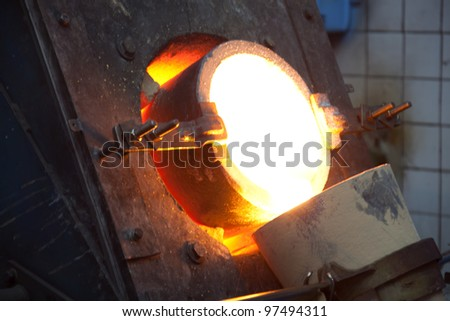 molten gold being poured from a foundry crucible - stock photo