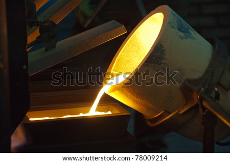 Molten Gold being poured into Ingot moulds - stock photo