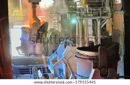 molten metal poured from ladle in factory - stock photo