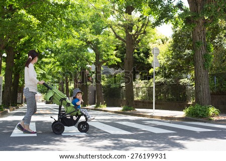mom and baby crossing the street - stock photo