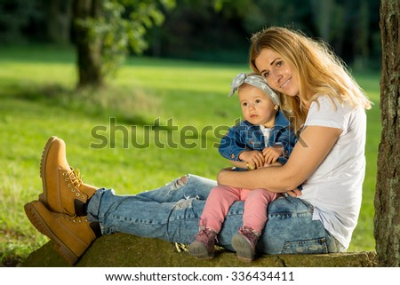 Mom and Baby girl daughter siting under the tree hugs love  - stock photo