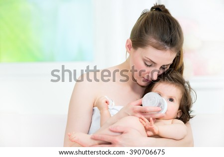 Mom and baby in a hug, baby drinking a milk from the baby bottle.Shallow doff