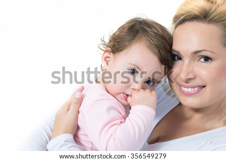 Mom and baby little girl hugging and looking at camera.White background.Copy space.Shallow doff - stock photo