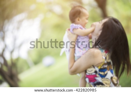 Mom and baby little girl on the blurry background - stock photo
