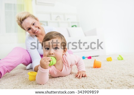 Mom and baby playing with a baby toys in a living room.Baby lying on front and looking at camera.Shallow doff, copy space - stock photo