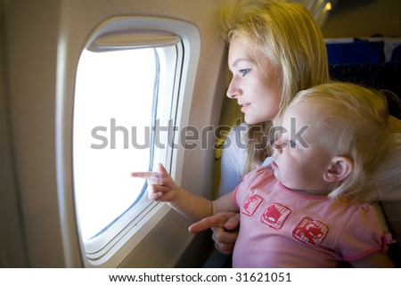 mom and child in the airplane - stock photo