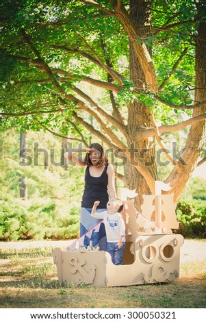 Mom and child playing in a cardboard boat. Summer day. The concept of a happy family - stock photo