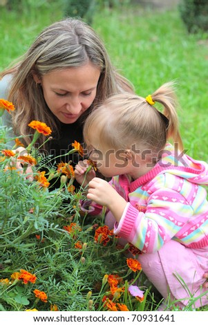 Mom and child sniffing flowers in the garden - stock photo