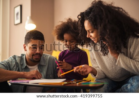 Mom and dad drawing with their daughter. - stock photo