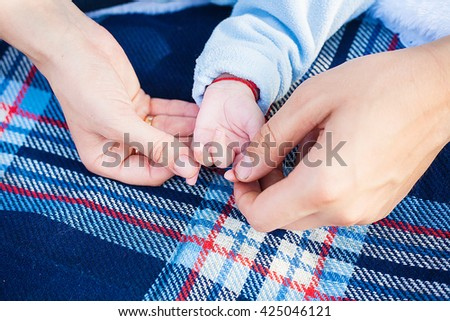 Mom and Dad hold the hand of his young child.