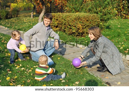 Mom and dad in the autumn park playing ball with their children - stock photo