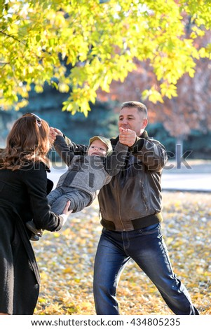 Mom and dad playing with a baby in the park in autumn. Cheerful baby at mum on hands fall.