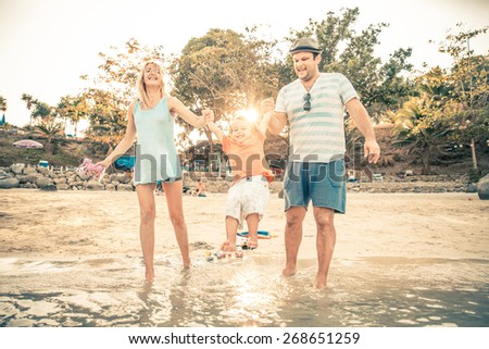 Mom and dad playing with their handsome son - Family and baby outdoors - stock photo