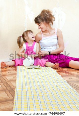 Mom and daughter are doing repairs together, wallpaper on the floor - stock photo