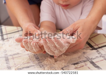 Mom and daughter are preparing homemade pizza in the kitchen