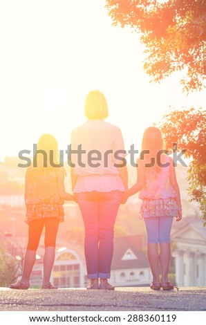Mom and daughter are twins at sunset when it is backlit and looking forward. Vintage family composition - stock photo