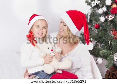 Mom and daughter at Christmas sitting near the fireplace in an embrace and smile - stock photo